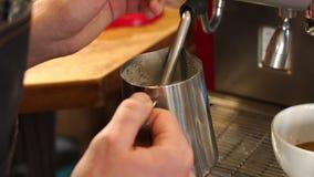 Barista που βράζει το γάλα στη καφετερία στον ατμό Το άτομο κάνει το αφρίζοντας γάλα σε μια μηχανή καφέ απόθεμα βίντεο