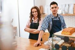 Barista και σερβιτόρα που λειτουργούν στον καφέ στοκ εικόνες