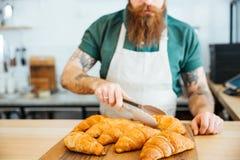Barista νεαρών άνδρων με τη γενειάδα που παίρνει τις croissant χρησιμοποιώντας λαβίδες Στοκ εικόνα με δικαίωμα ελεύθερης χρήσης