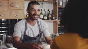 Barista που προσφέρει τον καφέ στον πελάτη στον καφέ απόθεμα βίντεο