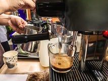 Barista χρησιμοποιώντας να προετοιμαστεί μηχανών καφέ τον αυτόματο φρέσκο καφέ ή το cappuccino και έκχυση στο φλυτζάνι γυαλιού στοκ εικόνα
