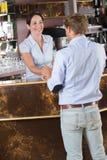 Barista говоря к человеку на счетчике бара в кафе Стоковое Изображение