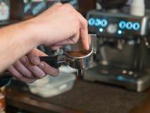 Barista делает кофе, конец вверх, на предпосылке машины кофе с мягким фокусом Руки бармена Стоковые Фотографии RF