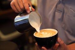 Barista используя кувшин кувшина для лить пененнсяое молоко к latte чашки кофе с картиной тюльпана на верхней части стоковая фотография