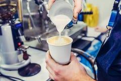 Barista используя машину кофе подготавливая свежий кофе и лить молоко к кофе эспрессо делает искусство latte в чашку белой бумаги Стоковое Фото