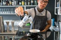 Barista льет кофе от бака кофе внутри современного кафа стиля дизайна с баром Стоковые Фотографии RF