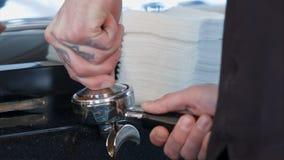 Barista отжимает земной кофе используя шпалоподбойку Стоковые Фото