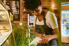 Barista проверяя запас в витрине десерта стоковая фотография