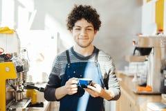 Barista усмехаясь и держа кофейную чашку около счетчика бара в ярком современном кафе стоковое фото rf