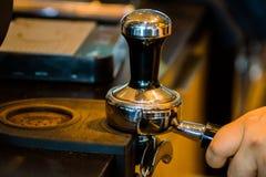 Barista утрамбовывает земли кофе в современной кофейне стоковое изображение