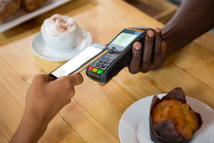 Barista accepting payment through mobile phone at cafe Royalty Free Stock Photo