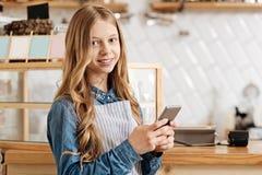 Barista adolescente precioso que presenta con el teléfono móvil Imagenes de archivo