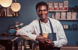 Barista africano que sorri na câmera que relaxa após o dia útil com café ao inclinar-se no contador na cafetaria foto de stock royalty free