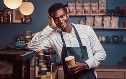 Barista africano que sorri na câmera que relaxa após o dia útil com café ao inclinar-se no contador na cafetaria fotos de stock royalty free