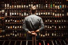 Barista alla cantina in pieno delle bottiglie con le bevande squisite fotografie stock