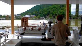 Barista At Arashiyama River. Stunning location for this modern coffee bar by the scenic banks of of Ooi River and Katsura River across the Arashiyama Mountain. I Stock Photos