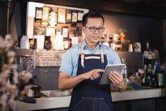 Barista asiático del hombre que sonríe con la tableta en su mano, employe femenino Fotografía de archivo libre de regalías