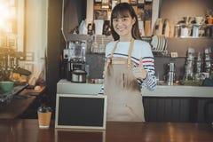 Barista asiático que se coloca en la barra contraria y mano que muestra el pulgar para arriba Foto de archivo libre de regalías