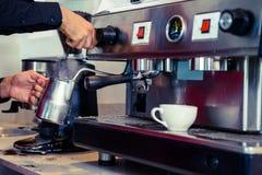 Barista att ånga mjölkar på kaffemaskinen Arkivbild