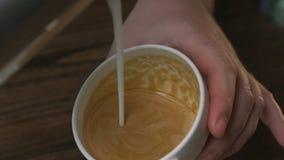 Barista att hälla mjölkar in i koppen kaffe som gör en modell lager videofilmer