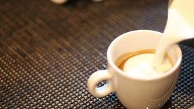 Barista att hälla mjölkar i varmt kaffe arkivfilmer
