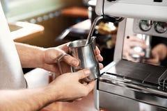 Barista att skumma mjölkar i metallkanna med kaffemaskintrollstaven på stångräknaren royaltyfria foton