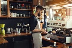 Barista att skumma mjölkar i metallkanna med trollstaven för kaffemaskinånga royaltyfri bild
