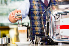 Barista in auslaufendem Espresso des Cafés schoss in Latte macchiato Lizenzfreie Stockfotografie