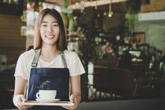 Barista azjatykcie kobiety wręczają trzymać świeżą kawy lub latte sztukę w białej filiżance przy sklep z kawą Obrazy Stock