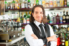 Barista or barman behind his bar Royalty Free Stock Photo
