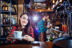 Barista bartender girl holds out cup of coffee in a bar Royalty Free Stock Images