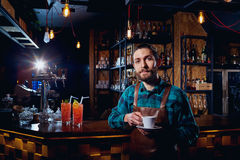 Barista, bartender hipster with a cup of coffee in  bar cafe.  Stock Photography