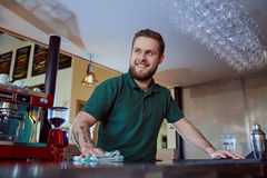 Barista bartender washes the surface of bar. royalty free stock photography