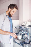 Barista with beard making coffee in a cafe Royalty Free Stock Photos