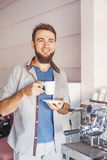 Barista with beard making coffee in a cafe Stock Images