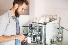 Barista with beard making coffee in a cafe Royalty Free Stock Photography