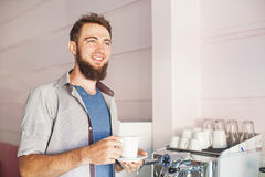 Barista with beard making coffee in a cafe Royalty Free Stock Images