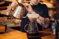 Barista bei der Arbeit in einer Kaffeestube Lizenzfreie Stockfotos