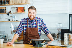 Barista bello felice in camicia a quadretti ed in grembiule marrone Immagine Stock