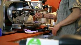 Barista bij professionele koffiemachine in koffiewinkel Art Barista wast en veegt espressomachine af alvorens kop te maken stock footage