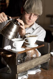 Barista Brewing a cup full. A  barista brews a single cup of coffee using a unique method and traditional style. the hot water drips through the filter and Royalty Free Stock Photography