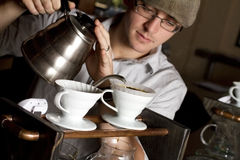 Barista brews a single cup. A coffee house employee brew a single cup of coffee using a unique system. The hot water drips through the filter. focus on brewing Stock Images