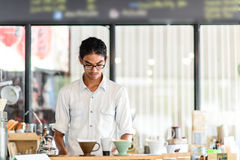 Barista brews a single cup a coffee house. Employee brew a single cup of coffee using a unique system. The hot water drips through the filter Stock Photography