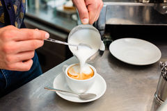 Barista in cafe or coffee bar preparing cappuccino. Barista in cafe or coffee bar preparing proper cappuccino pouring milk froth in a cup Stock Photo