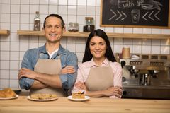 Barista and cafe owner with crossed arms. Portrait of smiling barista and cafe owner with crossed arms in coffee shop looking at camera Royalty Free Stock Images