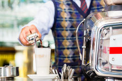 Barista in cafe pouring espresso shot in latte macchiato Stock Photography