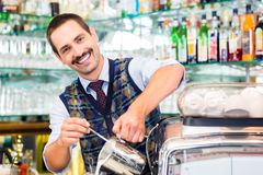 Barista in cafe pouring espresso shot in latte macchiato Royalty Free Stock Photos