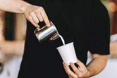 Barista carefully pours the milk into a glass in a modern coffee shop. royalty free stock photos