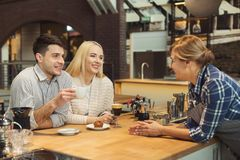 Barista chatting with the guests and serving coffee royalty free stock image