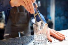 Barista che aggiunge cubetto di ghiaccio nel vetro alla barra Immagine Stock